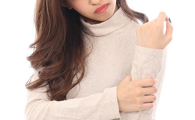 【手首・肘】手首が痛み押さえる女性