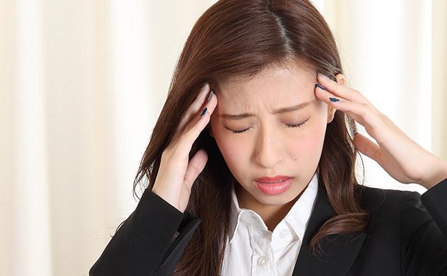【頭痛】頭痛に悩むビジネススーツの女性(アップ)