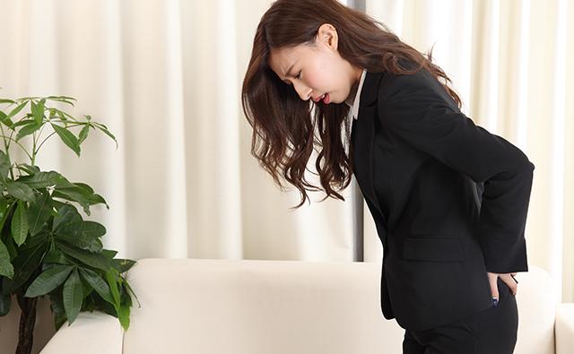 【腰痛】腰痛で仕事に支障が出ているビジネススーツの女性