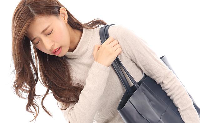 【肩こり】重い荷物を肩にかける女性