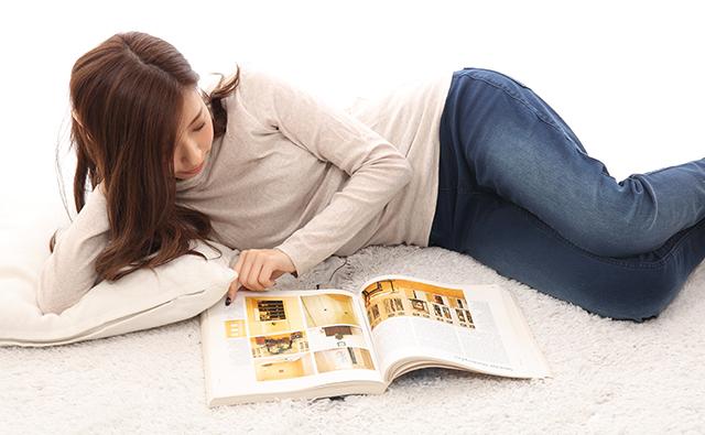 【生活】悪い姿勢で雑誌を見る女性