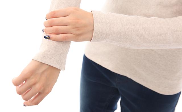 【手首・肘】手首が痛み押さえる女性(アップ)